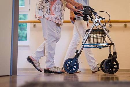 Eine Pflegekraft geht in einem Pflegeheim mit einer älteren Dame über einen Korridor. «Der Erhalt der Selbstbestimmung ist dringend notwendig. Es darf nicht passieren, dass Menschen entmündigt werden», sagt der Pflegebevollmächtigte der Bundesregierung, Andreas Westerfellhaus. Foto: Christoph Schmidt/dpa