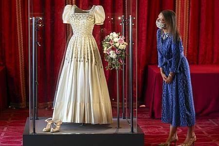 Caroline de Guitut, Kuratorin des Royal Collection Trust, wirft einen Blick auf das Hochzeitskleid von Prinzessin Beatrice. Foto: Steve Parsons/PA Wire/dpa