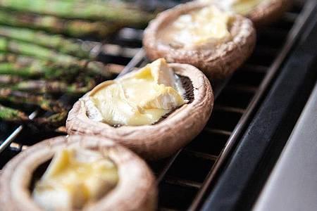 Gefüllte Champignons lassen sich auch gut grillen und sind das perfekte Fingerfood. Foto: Andrea Warnecke/dpa-tmn