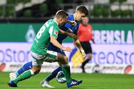 Werders Niklas Moisander (l) kämpft gegen Hoffenheims Christoph Baumgartner um den Ball. Foto: Carmen Jaspersen/dpa