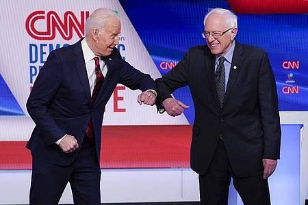 Bernie Sanders (r), und Joe Biden begrüßen sich mit ihren Ellenbogen. Foto: Evan Vucci/AP/dpa