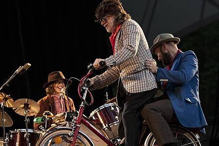 Helge Schneider fährt mit dem Gitarrist Henrik Freischlader auf dem Fahrrad auf die Bühne. Am Schlagzeug sitzt sein Sohn Charly. Foto: Fabian Sommer/dpa