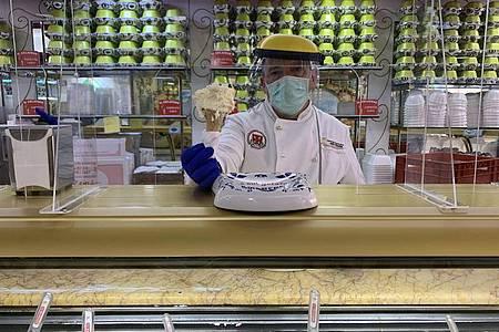 Paolo Costantini serviert mit Schutzausrüstung in seiner römischen Eisdiele ?Il Gelatone? Eis. Foto: Annette Reuther/dpa