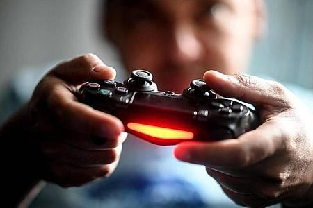 Sonys Playstation bring nach wie vor viel Geld in die Firmenkasse ein. Hier spielt ein junger Mann mit der Spielekonsole vor dem Fernseher. Foto: Britta Pedersen/dpa-Zentralbild/dpa