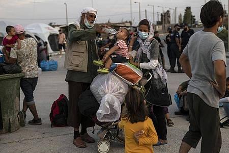 Ein Afghane gibt einem Kind Wasser. Die europäische Migrationspolitik steht heute mal wieder im Fokus. Foto: Petros Giannakouris/AP/dpa