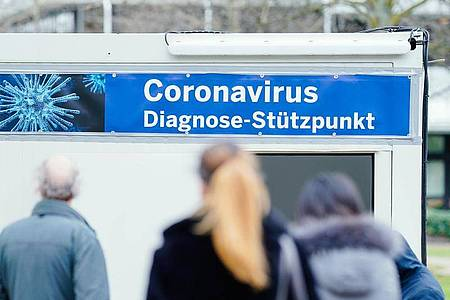 Menschen stehen auf dem Gelände des Universitätsklinikums Mannheim vor speziell für den Test auf das Coronavirus aufgestellten Containern. Foto: Uwe Anspach/dpa