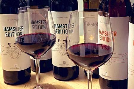 Zwei gefüllte Weingläser und Flaschen der «Hamster Edition» stehen auf einem Tisch beim Weingut Diehl. Foto: Weingut Diehl/dpa
