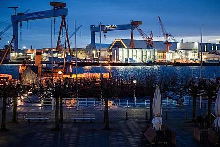Das beleuchtete Werftgelände von ThyssenKrupp Marine Systems am Ufer der Kieler Förde. Foto: Gregor Fischer/dpa