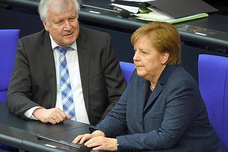 Horst Seehofer (l.) ist mit der Arbeit von Kanzlerin Angela Merkel sehr zufrieden. Foto: Sonja Wurtscheid/dpa