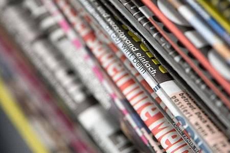 Ein Stapel Tageszeitungen in einem Büro auf einem Tisch. Foto: Ralf Hirschberger/dpa