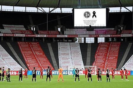 Vor dem Geister-Finale gedachten die beiden Mannschaften den Corona-Opfern. Foto: Annegret Hilse/Reuters/POOL/dpa
