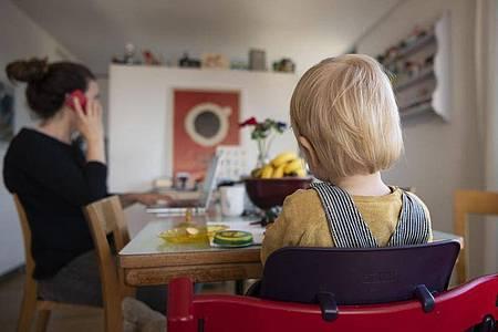 Eine Frau sitzt im Homeoffice an ihrem Laptop und telefoniert, während ihr Kind neben ihr in einem Kinderstuhl am Tisch sitzt. Foto: Christian Beutler/KEYSTONE/dpa