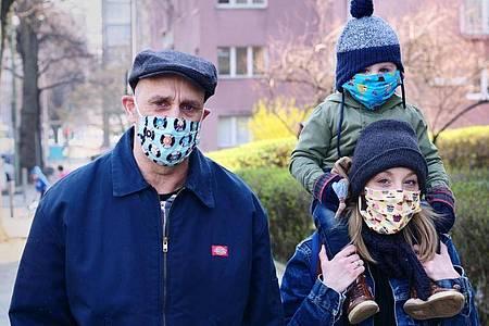 Eine Familie geht in Berlin-Friedenau spazieren. Alle Familienmitglieder tragen dabei Masken, als Schutz gegen das Coronavirus. Foto: Wolfram Steinberg/dpa