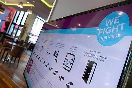 Auf einem Bildschirm in der Lobby des Leonardo Royal Hotels in München sind die Hygienemaßnahmen nachzulesen. Foto: Sven Hoppe/dpa