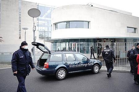 Ein Auto steht vor dem Tor des Bundeskanzleramts. Auf der Tür ist die Aufschrift «Stop der Globalisierungs-Politik» zu lesen. Foto: Michael Kappeler/dpa