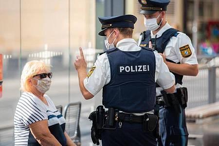Zwei Polizisten nehmen an einer Tram-Haltestelle in Würzburg von einer Frau nach einem Verstoß gegen die Maskenpflicht im öffentlichen Nahverkehr die Personalien auf. Foto: Nicolas Armer/dpa