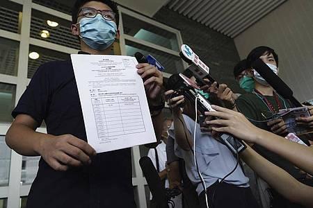 Aktivist Joshua Wong zeigt Journalisten die Nominierungsunterlagen für die Parlamentswahl im September. Foto: Vincent Yu/AP/dpa