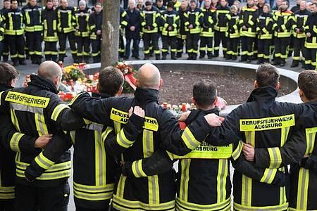 Feuerwehrmänner trauern am Königsplatz in Augsburg. Foto: Stefan Puchner/dpa/Archiv