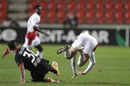 Leverkusens Karim Bellarabi (l) foult Slavias Lukas Provod und kassiert im Anschluss die Rote Karte. Foto: Petr David Josek/AP/dpa