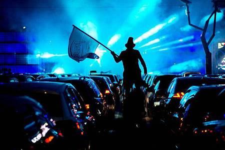 Ein Akteur läuft während der Auto-Disco auf Stelzen durch die Wagenreihen. Foto: Hauke-Christian Dittrich/dpa