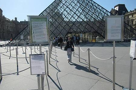 Absperrungen und Anweisungen vor dem Eingang des Louvre. Foto: Sabine Glaubitz/dpa