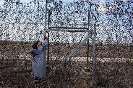 Ein Migrant versucht an der türkisch-griechischen Grenze, mit einer Drahtschere den Zaun durchzuschneiden. Foto: Yasin Akgul/dpa