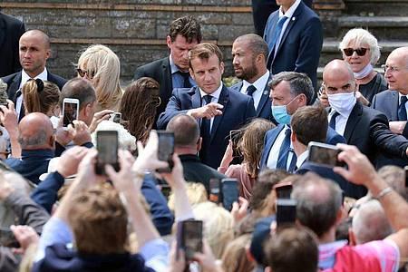 Emmanuel Macron (hinten,M) nach der Stimmabgabe im nordfranzösischen Seebad Le Touquet. Foto: Ludovic Marin/AFP/dpa