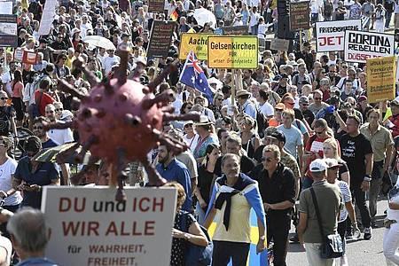 Teilnehmer einer Demonstration protestieren mit Schildern auf den Rheinwiesen gegen die Maßnahmen zur Bekämpfung des Coronavirus. Foto: Roberto Pfeil/dpa