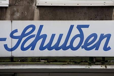 Der Schriftzug «Schulden» steht über einem leeren Ladenlokal. Die Schuldenuhr des Bundes der Steuerzahler tickt so schnell wie nie zuvor. Foto: Rolf Vennenbernd/dpa