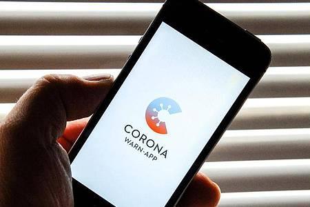 Auf dem Bildschirm eines Apple iPhone SE ist der vom Presse- und Informationsamt der Bundesregierung herausgegebene Startschirm einer Corona Warn-App abgebildet. Foto: Stefan Jaitner/dpa