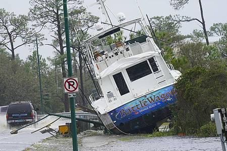 Ein Boot ist durch den Hurrikan «Sally» an Land gewirbelt worden und liegt nun neben einer Straße. Foto: Gerald Herbert/AP/dpa