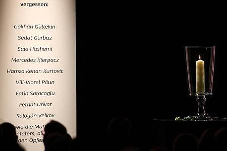 Eine Kerze steht neben den Namen der Opfer bei der Gedenkfeier für die Opfer von Hanau. Foto: Kai Pfaffenbach/Reuters-Pool/dpa