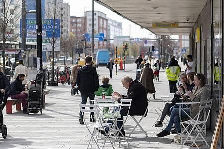 Menschen sitzen im Stadtzentrum von Stockholm vor einem Eiscafe. Foto: Ali Lorestani/TT News Agency/AP/dpa
