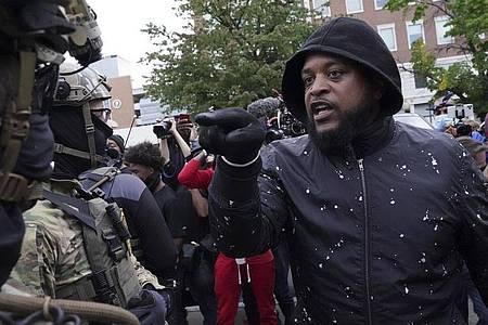 Ein Demonstrant in der US-Stadt Louisville hat eine Auseinandersetzung mit einem Sicherheitsbeamten. Foto: John Minchillo/AP/dpa