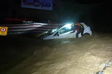 Ein Feuerwehrmann arbeitet im italienisch-französischen Alpenübergang Colle di Tenda an einem Auto, das im Eingang eines Tunnels im Hochwasser feststeckt. Foto: --/Vigili del Fuoco/dpa