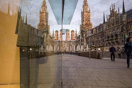 Passanten gehen über den Marienplatz in der Münchner Innenstadt. Hintergrund sind die Zwillingstürmen der Frauenkirche (l) und das Neue Rathaus (r) zu sehen. Foto: Peter Kneffel/dpa