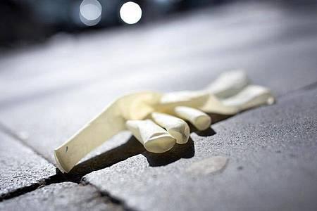 Eine weggeworfener Einweg-Schutzhandschuh auf einem Gehweg in Düsseldof. Foto: Martin Gerten/dpa