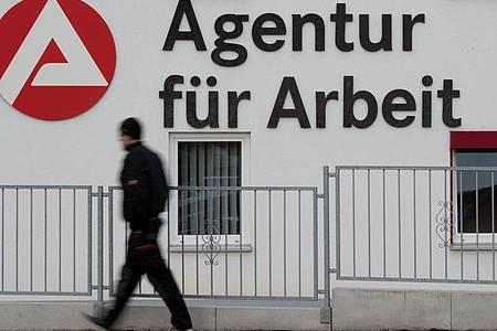 Ein Mann geht an dem Logo der Agentur für Arbeit vorbei. Foto: Sebastian Kahnert/dpa-Zentralbild/dpa