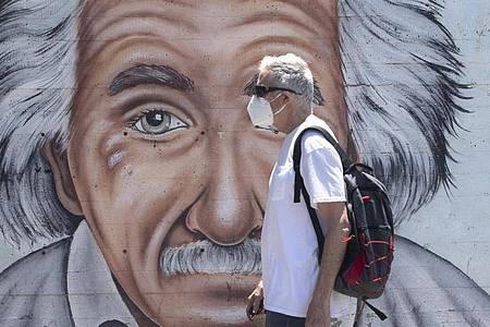 Ein israelischer Mann, der einen Mund- und Nasenschutz trägt, geht an einem Wandbild vorbei, das Albert Einstein zeigt. Foto: Sebastian Scheiner/AP/dpa