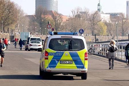 Die Polizei kontrolliert an der Rheinufer Promenade in Düsseldorf die Einhaltung der Vorsichtsmaßnahmen gegen die Coronavirus-Pandemie. Foto: David Young/dpa