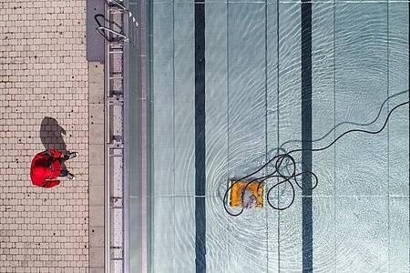 Ein Badleiter steht in einem Freibad am Beckenrand, und prüft die Arbeit eines Pool-Reinigungsroboters. Foto: Patrick Pleul/dpa-Zentralbild/dpa