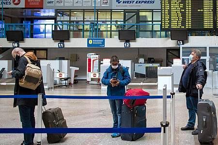Passagiere mit Smartphones in einer Schlange im Internationalen Flughafen von Vilnius. Foto: Mindaugas Kulbis/AP/dpa