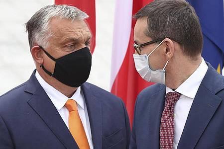 Polens Premierminister Mateusz Morawiecki begrüßt seinen ungarischen Amtskollegen Viktor Orban. Eine Mehrheit der EU-Staaten hat ungeachtet von Drohungen aus Ungarn und Polen ein Verfahren zur Bestrafung von Verstößen gegen die Rechtsstaatlichkeit innerhalb der Union auf den Weg gebracht. Foto: Czarek Sokolowski/AP/dpa