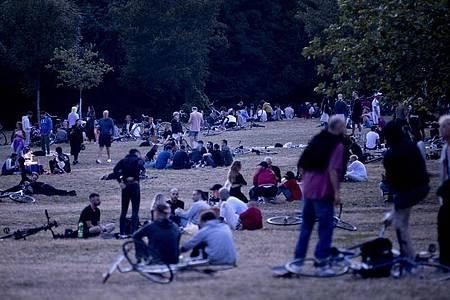 Menschen sitzen nachts im Volkspark Hasenheide auf einer Wiese. Foto: Christoph Soeder/dpa