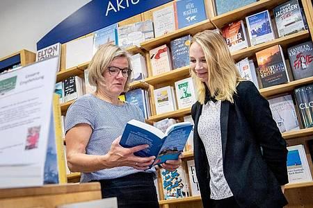 Gibt ihr Fachwissen gerne weiter: Christiane Schulz-Rother, Inhaberin der Tegeler Bücherstube in Berlin, bespricht sich mit ihrer Auszubildenden Sophie Schmale (r). Foto: Zacharie Scheurer/dpa-tmn