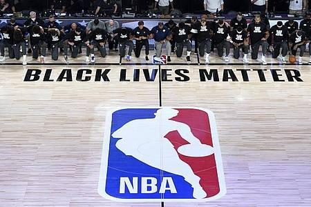 Alle Spieler der New Orleans Pelicans und von Utah Jazz knien vor einem «Black Lives Matter»-Schriftzug. Foto: Ashley Landis/Pool AP/dpa