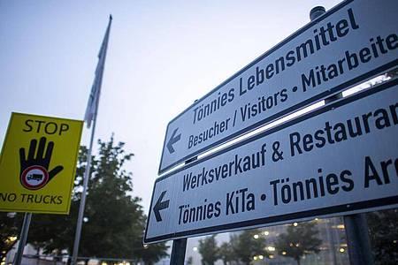Schilder weisen den Weg zum Hauptgebäude, zu Werksverkauf, Kita und Tönnies Arena auf dem Gelände des Fleischwerks Tönnies. Foto: David Inderlied/dpa