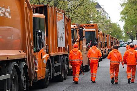 Mitarbeiter der Berliner Stadtreinigung gehen an abgestellten BSR-Fahrzeugen vorbei. In Potsdam werden die Tarifverhandlungen für den Öffentlichen Dienst Mitte September fortgesetzt. Foto: Paul Zinken/dpa