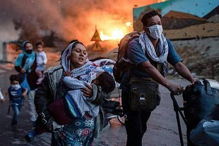 Bewohner des Flüchtlingslagers Moria fliehen vor den Flammen. Foto: Petros Giannakouris/AP/dpa