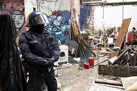 Ein Polizist steht nach der Räumung im Innenhof des ehemals besetzten Hauses «Liebig 34». Das Eckhaus an der Liebigstraße im Stadtteil Friedrichshain soll geräumt und an den Besitzer übergeben werden. Foto: Fabian Sommer/dpa